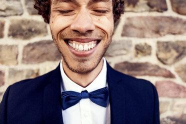 Happy gay man against brick wall - MASF03059