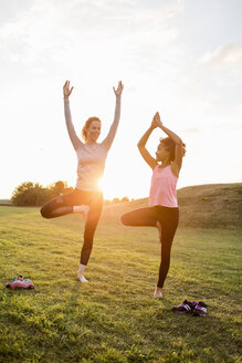 Happy mother and daughter practicing yoga on grass at park during sunset - MASF03065