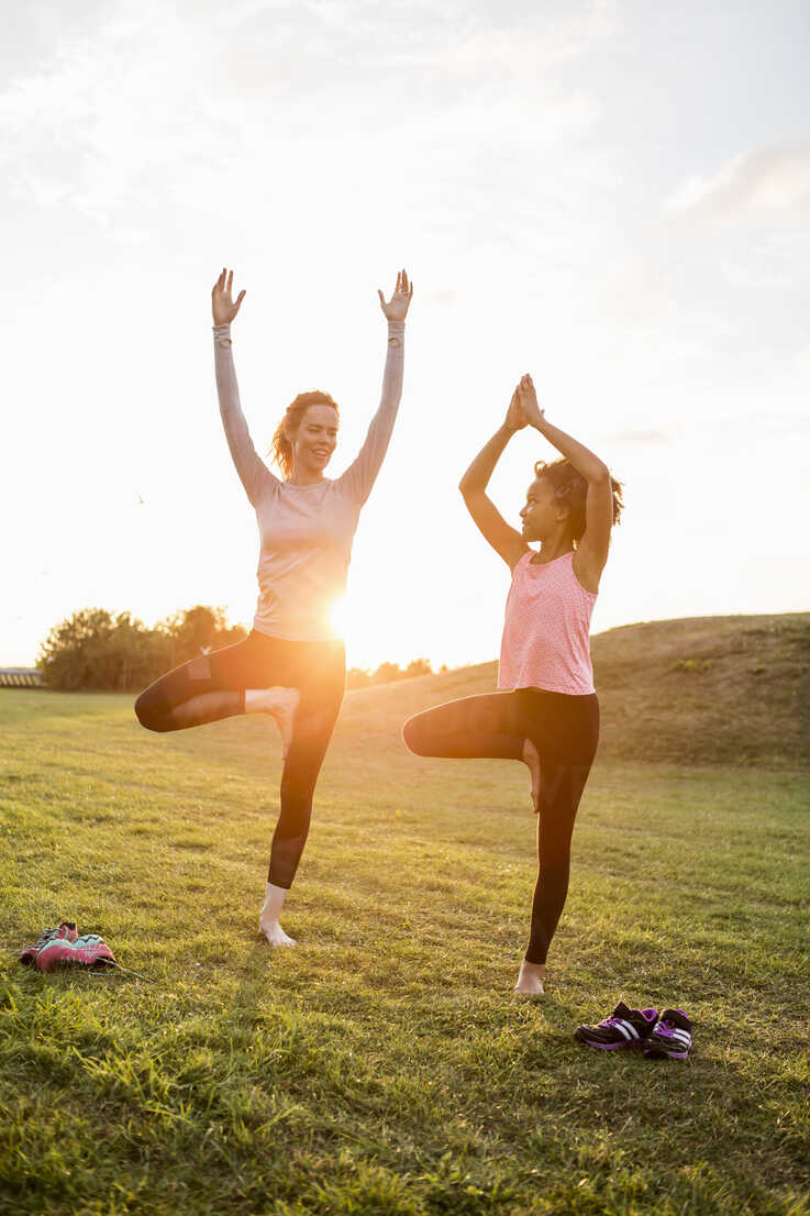 Happy mother and daughter practicing yoga on grass at park during sunset - MASF03065 - Kentaroo Tryman/Westend61