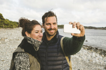 Happy couple taking selfie at beach against sky during sunset - MASF03068