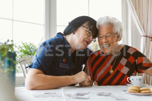 Happy caretaker and senior woman sitting at table - MASF03074