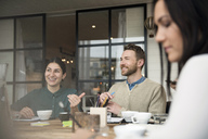 Happy business people talking while having coffee at table during meeting in office - MASF03080