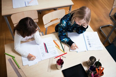 High angle view of schoolgirls studying at desk in school - MASF03098