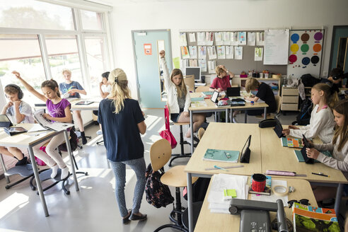 High school students raising hands with teacher in classroom - MASF03104