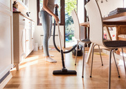 Low section of teenage girl cleaning hardwood floor with vacuum cleaner at home - MASF03110