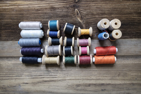 Overhead view of various thread spools on wooden table - CAVF36465