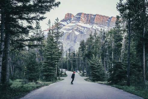 Woman skateboarding on country road amidst trees against mountains at Banff National Park - CAVF36561