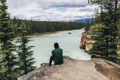 Man looking at view while sitting on cliff at Jasper National Park - CAVF36564