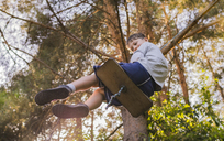 Low angle view of boy swinging at park - CAVF36570