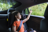 Cute boy playing with toy rocket on back seat of car - CAVF36576