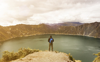 Man standing on cliff against Quilotoa and cloudy sky - CAVF36600