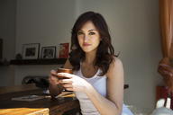 Portrait of beautiful woman holding coffee cup and sitting by table at home - CAVF36636