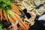 Cropped image of woman using phone while buying carrots in supermarket - MASF03117