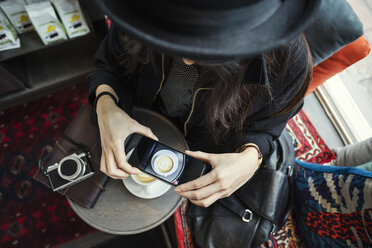 Directly above shot of young woman photographing coffee through smart phone in creative office - MASF03120
