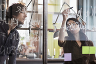 Creative businesswoman writing on glass while explaining to colleague in office - MASF03126