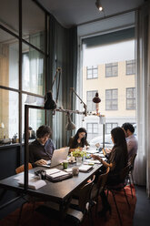 Creative business team sitting at table working in modern office - MASF03129