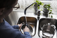 Cropped image of man washing utensils at kitchen sink - MASF03138