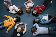 Directly above shot of school children lying on floor in classroom - MASF03141