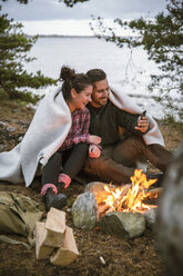 Couple wrapped in blanket using mobile phone while sitting by fire pit at campsite - MASF03159