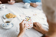 Cropped image of senior woman playing cards with family at table - MASF03165