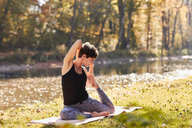 Mid adult woman in forest practicing yoga - SHOF00005