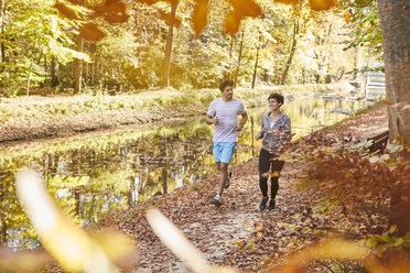 Couple jogging on autumnally forest track - SHOF00017