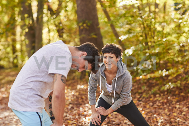 Couple stretching in autumn forest - SHOF00020