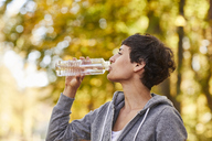 Woman drinking from water bottle - SHOF00023