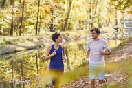 Couple jogging on autumnally forest track - SHOF00026