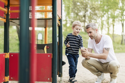 Father showing smart phone to son while enjoying at playground - MASF03169