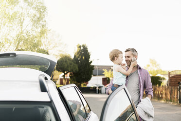 Father carrying son with stuffed toy while standing by car on street - MASF03172
