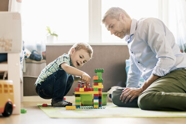 Father and son playing with toy blocks while sitting at home - MASF03175