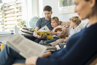 Father reading story book to kids with mother sitting in living room - MASF03178