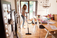 Full length of teenage girl cleaning hardwood floor with vacuum cleaner at home - MASF03181
