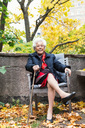 Full length portrait of happy senior woman sitting on chair in park - MASF03190