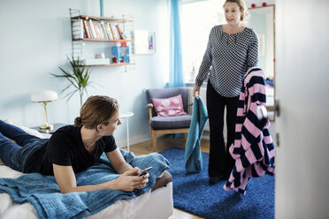 Angry woman holding clothes while looking at son lying on bed at new home - MASF03211
