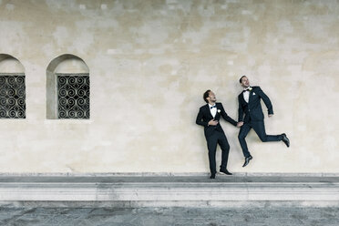 Cheerful man jumping while holding hands of gay partner on bench against wall - MASF03214