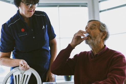 Caretaker looking at senior man taking medicine - MASF03223