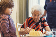 Boy and great grandmother looking at sponge cake in house - MASF03226