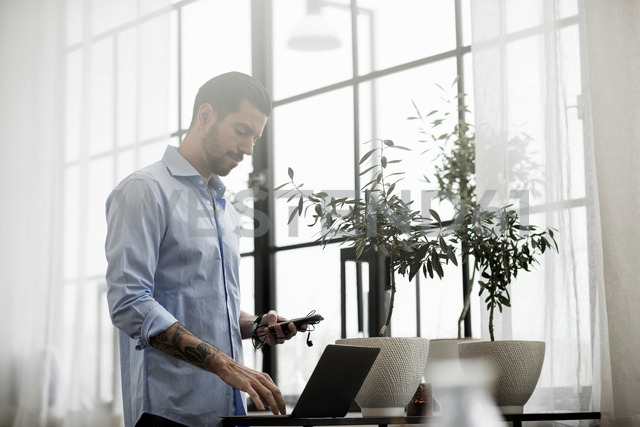 Businessman using technology while standing at table in office - MASF03232
