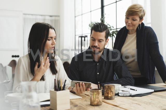 Business colleagues looking at smart phone held by woman during meeting - MASF03241