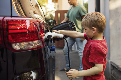 Boy charging electric car against father standing by house - MASF03244