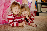 Portrait of cute sisters lying on rug at home - CAVF36735