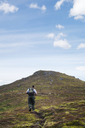 Rear view of man with backpack walking on mountain against sky - CAVF36747