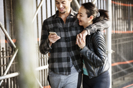 Happy loving couple using smart phone while walking on footpath - CAVF36804
