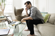 Happy businessman using smart phone while sitting on sofa at home - CAVF36816