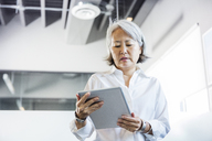 Low angle view of businesswoman using tablet computer in office - CAVF36825