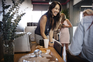 Cheerful businesswoman sitting on table in office canteen - CAVF36855