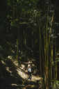 Rear view of woman standing on field in forest - CAVF36960