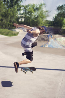 Young man doing skateboard trick on ramp - CAVF36993